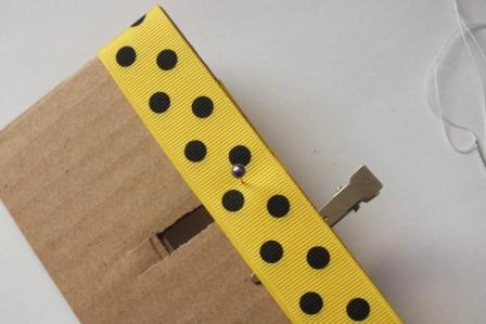 Лентой обкрутите картон, а в середине вырезанной линии проткните её иголкой. Далее снимите ленту, при этом, не трогая иголку.