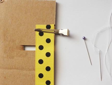 Возьмите ленту в 2,5 см и с помощью зажима прикрепите её к краю картона возле выреза.