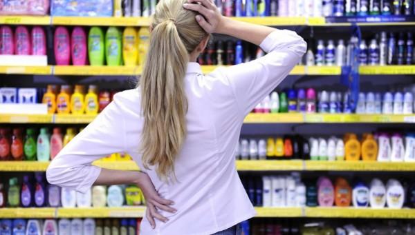 Фото девушки, озадаченной выбором моющего средства для локонов, так как ассортимент просто огромен.
