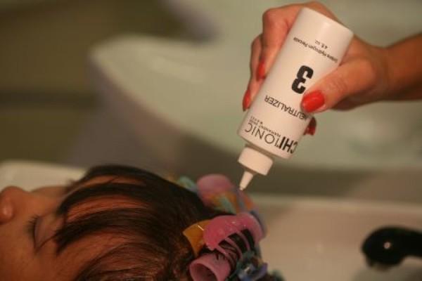 Фото нанесения фиксирующей смеси в процессе проведения химической завивки мастером в салоне красоты