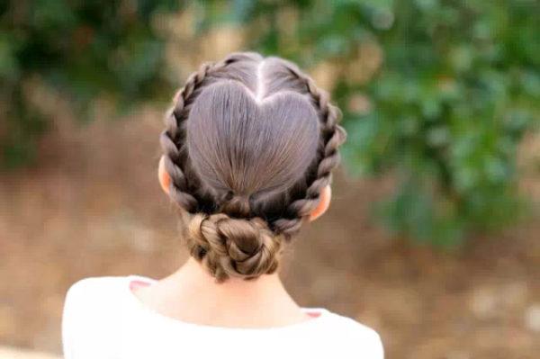 Коса – сердечко, украшенная пучком, подойдет для более взрослых барышень
